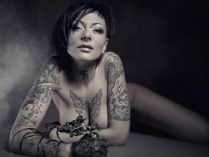 Beautiful woman with many tattoos posing indoors