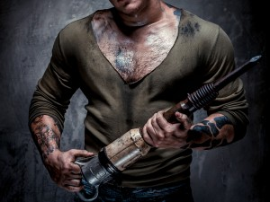 Muscular tattooed man with jackhammer posing over grey backgroun